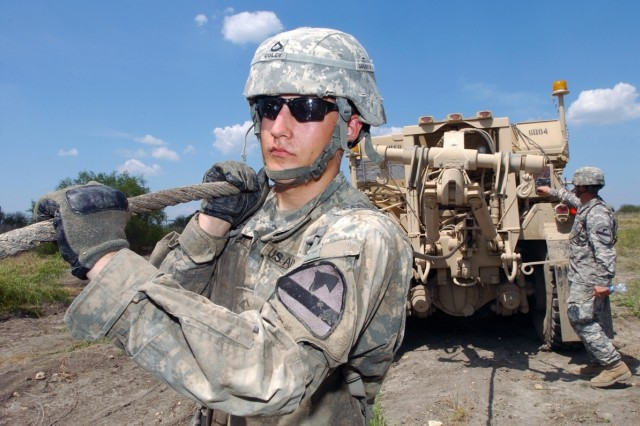 Pfc. Justin Coley, a metal worker assigned to the Service and Recovery Shop, Company B, 15th Brigade Support Battalion, 2nd Brigade Combat Team, 1st Cavalry Division of Mineral Wells, Texas, pulls out a wench cable during recovery training Aug. 14, 2008.