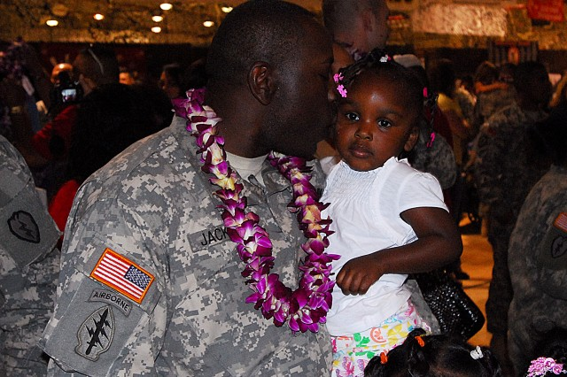 Pvt. Kendell Jackson kisses his daughter, Mekellia, who turns three on Monday.  Jackson was among 400 2nd Stryker Brigade Combat Team Soldiers who returned home to Hawaii following a 15-month deployment to Iraq late Tuesday night, Feb. 17 at the Wheeler Army Airfield Multiple Deployment Facility.