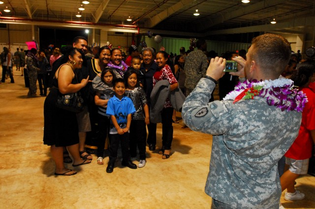 A 25th Infantry Division Soldier takes a picture of Sgt. Aloma Siataga, a native of Honolulu, Hawaii, and her family following a redeployment ceremony Feb. 17 at the Wheeler Army Airfield Multiple Deployment Facility.  More than 400 2nd Stryker Brigade Combat Team Soldiers returned to Hawaii after a 15-month deployment to Iraq.