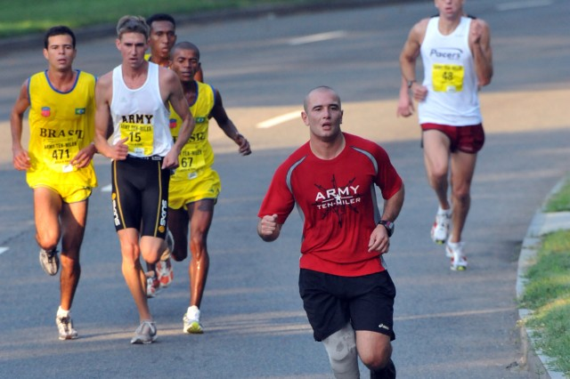 Army Ten-Miler leaders Pvt. Reginaldo Campos Jr. of the Brazilian Army (471), U.S. All-Army 1st Lt. Philip Sakala (15) and Brazilian Joseuldo Nascimento (67) close the gap on a member of the Missing Parts in Action team during the 24th running of the Army Ten-Miler, Oct. 5.