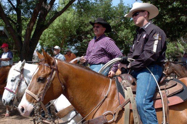 Spc. Jake Lowery (right) and his stepfather, John Escobedo, watch competitors while awaiting their turns in the Troy Shelley Affiliate team-roping event, May 10, at Denny Calhoun Arena in Las Cruces, N.M. Grandfather Pete Escobedo (white mustache) looms in the backdrop. All three competed in the event.