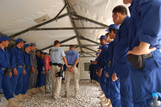 US and German police mentor the Afghan National Police on the proper use of hand-restraints on suspects at the Konduz regional police training facility in the summer of 2008.