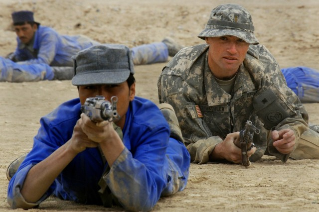 Army 2nd Lieutenant Jean Leimkuler coaches an Afghan National Policeman during a tactical movement exercise. Leimkuhler is a member of a police mentoring team and works with ANP officers from Zhari district in Kandahar Province as part of  Focused District Development.