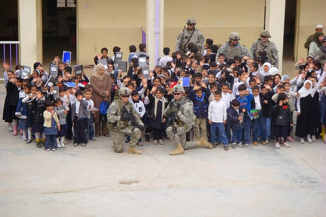 SADR CITY, Iraq - Students of the Al Aqbas Elementary School smile and wave during a group picture at the school's courtyard Feb. 9 in the Sadr City district of eastern Baghdad. Soldiers assigned to the 1st Battalion, 6th Infantry Regiment, distributed the supplies after receiving donations from Girl Scout troops in Larchmont, N.Y.