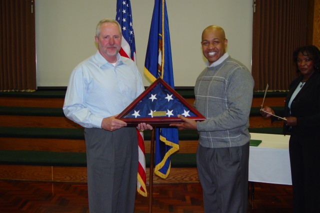 Brig. Gen. Larry Wyche, commanding general of the Joint Munitions Command, recognizes Rodney J. Huff, deputy to the commander, Tooele Army Depot during RodAca,!a,,cs retirement dinner Feb. 12.