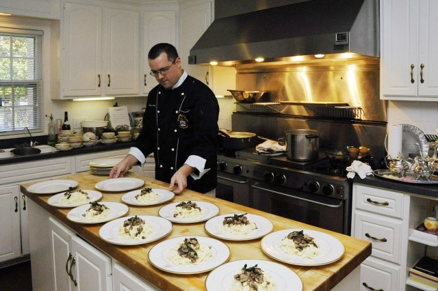 Sgt. 1st Class David Montag prepares plates for a dinner at the Combined Arms Center commander's quarters at Fort Leavenworth, Kan..