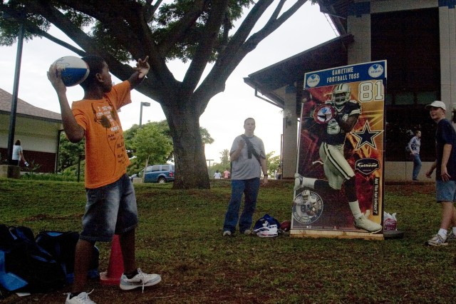 ALIAMANU MILITARY RESERVATION, Hawaii - Ahmed Abdullah, 11, shows off his football skills, tossing the pigskin to a cardboard cutout of Dallas Cowboys' wide receiver Terrell Owens, in hopes of winning a prize. The Meet and Greet was held in conjunction with the Family and Morale, Welfare and Recreation's (FMWR) expo, Feb. 4, which provided family members with information regarding programs and services available on Army-Hawaii installations.