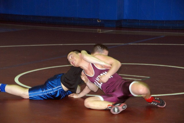 Patrick Rautert (left) holds down his opponent, Justin Uno, in the championship match of the wrestling tournament held Feb. 14 at the USAG Red Cloud, South Korea, Fitness Center. Rautert went undefeated during the tournament to win first place followed by Uno and Ryan Wilson in third.