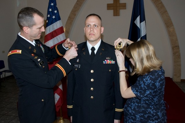 U.S. Army Garrison Livorno Commander, Lt. Col. Steven Cade (left) and Mrs. Rachel Porter pin major rank on Chaplain (Maj.) Kelly Porter as his family in Kentucky watched via live teleconference.