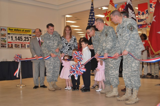Staff Sgt. Emilio Granados and his Family cut the ribbon at the new Post Exchange Feb. 13 at Camp Forsyth. Along with the Granados were Edward Bouley, AAFES senior vice president; Maj. Gen. Keith Thurgood, AAFES commander; Col. Ricky Gibbs, 1st Inf. Div. chief of staff; Stan Young, AAFES general manager at Fort Riley; and Col. Richard Piscal, Fort Riley garrison commander.