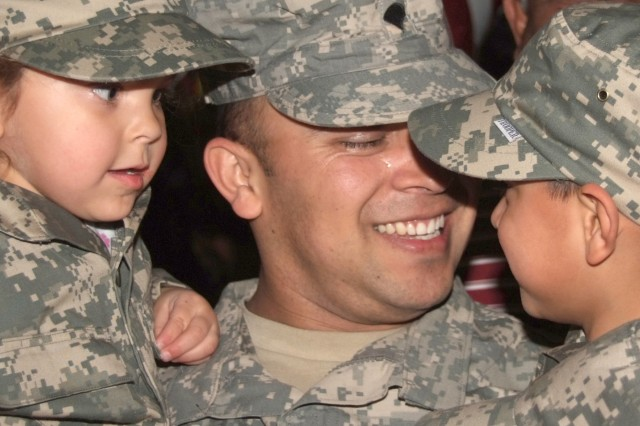 FORT CARSON, Colo.-Spc. Ramon Ortiz reunites with his 3-year-old twins, Makayta and Derek Ortiz, during the Feb. 6 welcome-home ceremony for 300 3rd Brigade Combat Team, 4th Infantry Division Soldiers at the Fort Carson Special Events Center.