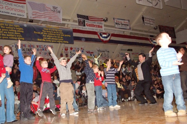 FORT CARSON, Colo.-Fort Carson USO Program Manager Phil Martinez, right, leads Family and friends in performing the YMCA dance Feb. 6 at the Special Events Center prior to the arrival of more than 300 Soldiers with 3rd Brigade Combat Team, 4th Infantry Division.