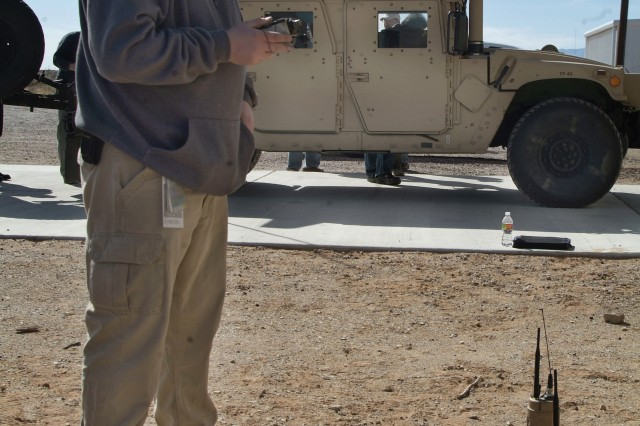 Chris Fagan, a system test engineering specialist with Textron Defense System, tests the connections between a pair of tactical unattended ground sensors and the network integration kit-equipped Humvee behind him. The unattended ground sensors will allow for smaller numbers of Soldiers to monitor larger areas.