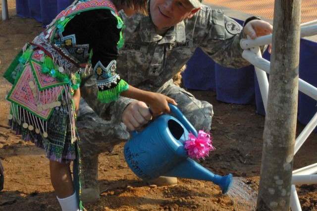 BANSAKRIKUK, Thailand - U.S. Army Maj. Gen. Patrick Wilson, deputy commanding general of Cobra Gold 09, is assisted in watering a newly planted tree by a girl from the village of Bansakrikuk. The tree was planted in front of a future school built completely by a joint effort of U.S. and Thai militaries during Exercise cobra Gold.