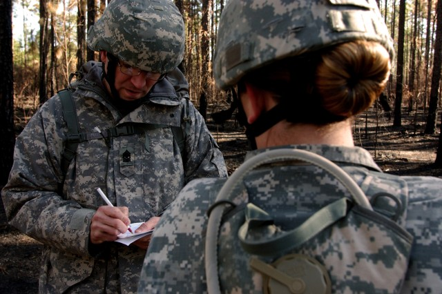 Sgt. Maj. Malcolm Wolfe, a command chaplain assistant, works with Spc. Gina Jenkins, from Miami and a finance specialist, both assigned to the 81st Regional Support Command., before embarking on a two-hour land navigation course at Fort Jackson, S.C. The command used the weekend battle assembly to sharpen several Soldier skills along with performing their mission of base operations for the southeastern portion of the U.S.