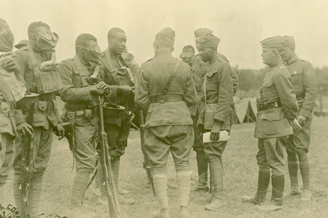 Members of the 366th Infantry Regiment take part in a gas mask inspection and training drill in France during World War I. (WWI Signal Coprs Photograph Collection).