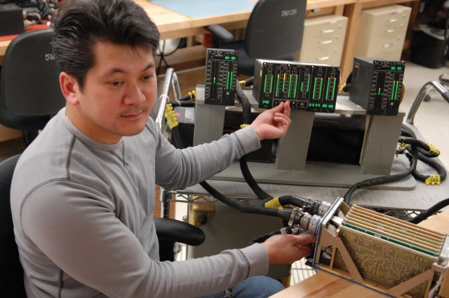 Trung Mai, electronics mechanic, uses a test set to troubleshoot one of two signal data converters in the Vertical Instrument Display System.