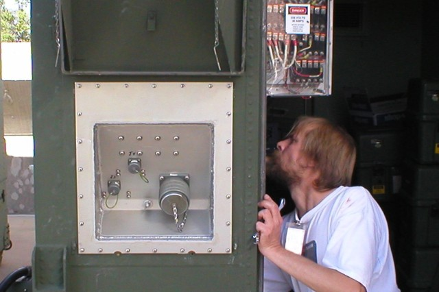 Electronics Mechanic Anthony Lindstrom works on a AN/TRC-194 Milstar Ground Command Post.  A Tobyhanna-installed power entry panel is seen on the outside.