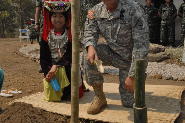A student at the Baan Hauxtontong School in northern Chiang Mai Province, Thailand, looks on as Lt. Gen. Benjamin Mixon, commander U.S. Army Pacific, plants a tree during the dedication of the school's new building Feb. 17. The three-classroom, multi-purpose building was the last of six constructed by Thai and U.S. military engineers during Exercise Cobra Gold.