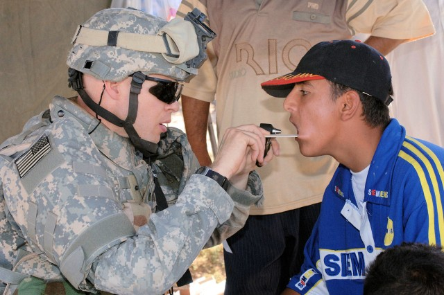 Capt. James Mitchell examines a man's teeth in Baghdad. The Army has identified a shortage of medical specialists in the ranks, and is using the Military Accessions Vital to the National Interest pilot recruiting program to bring in more doctors and other skilled medical professionals from among legal aliens in the United States.