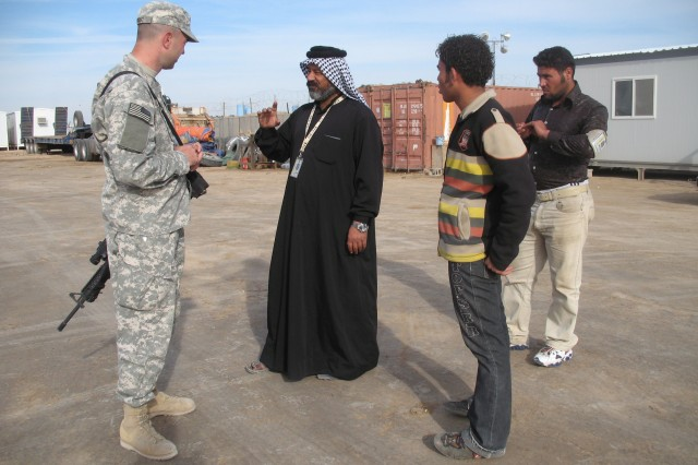 287th Sustainment Brigade IBIZ (Iraqi-Based Industrial Zone) Manager 1st Lt. Andrew Wright, , ITC officer in charge, 287th Sust. Bde., and native of Paola, Kan. hears Al-Ghezy Trucking and General Contracting Company owner Jameel Jabir's  (wearing traditional Iraqi clothing) plans to expand his operations at the IBIZ complex, Feb. 5.  Standing behind Jabir are members of his staff, Ali Haider and Mustafa Jameel. (U.S. Army photos by Master Sgt. Carl K. Mar)