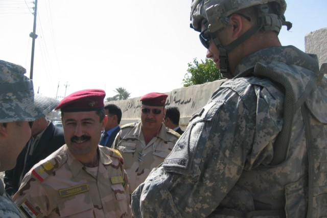 Baghdad - Lt. Col. Tahseen (left), commander, 2nd Battalion, 55th Brigade, 17th IA Division and Capt. Allan Carroll (right), of Kailua, Hawaii, commander, Company B, 1st Battalion, 35th Armor Regiment, meet outside the clinic in Adwaniyah, Feb. 18.  Soldiers from Multi-National Division-Baghdad and their 17th Iraqi Army Division partners provide a life changing experience to Iraqi children with the delivery of over a dozen new wheelchairs.