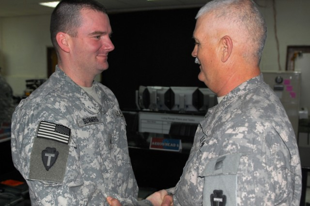 BAGHDAD - Sgt. Jason Summers (left), with Headquarters and Headquarters Company, 56th Infantry Brigade Combat Team, 36th Infantry Division, receives a handshake of congratulations from Command Sgt. Maj. John Morgan III, senior enlisted leader, 56th IBCT, following his promotion into the Corps of Non-Commissioned Officers. Summers, a Texas Army National Guard Soldier from Justin, Texas said after his promotion that he would live the NCO Creed and that he would not let his leaders down.