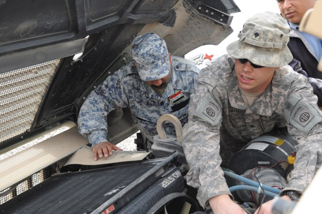 JOINT SECURITY STATION BELADIYAT, Iraq - Spc. Christopher Parker (right), a native of Portland, Tenn., assigned to 2nd Battalion, 505th Parachute Infantry Regiment, 3rd Brigade Combat Team, 82nd Airborne Division, uses a multi-meter device to check the electrical components under the hood of an up-armored humvee while training National Police mechanics assigned to the 8th Brigade, 2nd NP Div., during a maintenance training event Feb. 21 at Joint Security Station Beladiyat in eastern Baghdad.