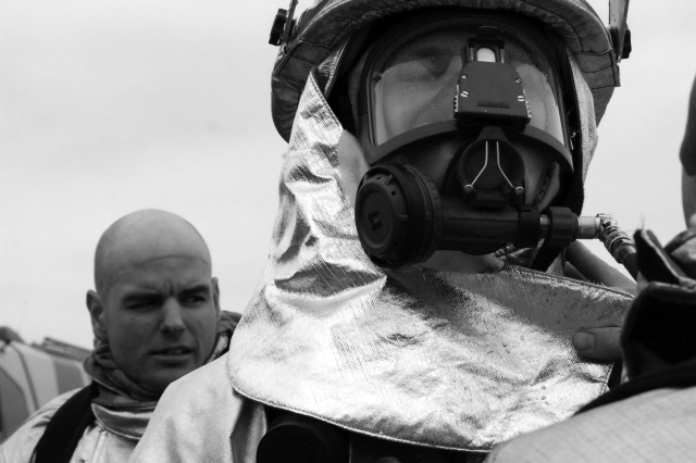 Staff Sgt. Cameron Stone and Tech Sgt. Jedadiah Moss remove their gear, after experiencing the intense heat from the flames inside the fuselage.