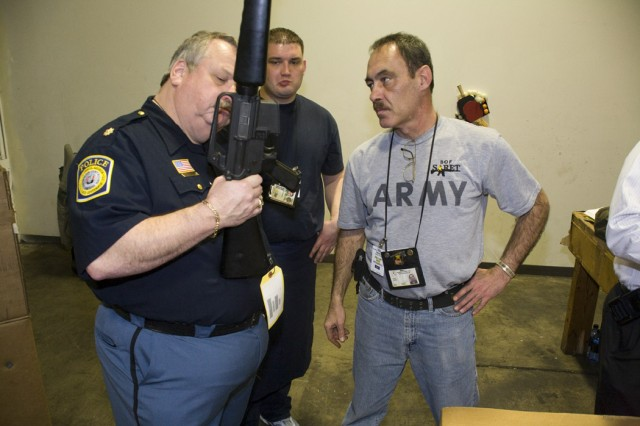 Maj. Stan Swiney, a police officer from Columbus, Ga., holds up an M16 rifle and talks about its capabilities with representatives from the Department of Defense at Anniston Army Depot.