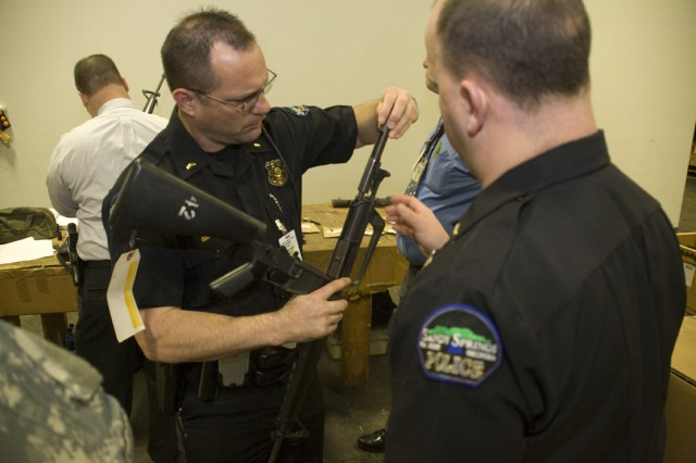 Two law enforcement officers look at one of the M16 rifles they're planning to receive from the Defense Logistics Agency.