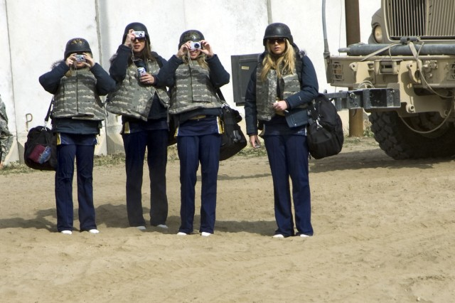 Three cheerleaders with the St. Louis Rams of St. Louis, Miss. take pictures of combat outpost Courage's main building, a palace that was at one time inhabited by one of Saddam Hussein's daughters in Mosul, Iraq. The grounds are now used by assets of 2nd Battalion, 82nd Field Artillery Regiment as their headquarters and living area. The cheerleaders toured the Ninewa province Feb. 18, meeting Soldiers with the 3rd Heavy Brigade Combat Team, 1st Cavalry Division that don't live on the main forward operating bases or have access to commodities that those FOBs boast.