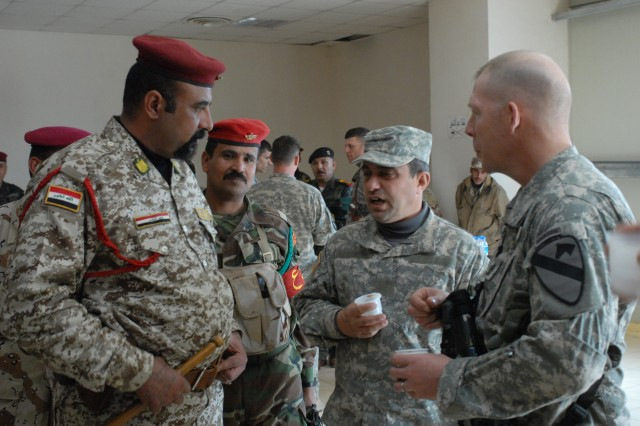 A translator stands between two Sgts. Maj. at a meeting at K-1, a military base in Kirkuk Province, Feb. 5. The 12th Iraqi Army Division and 2nd Brigade Combat Team, 1st Cavalry Division, will be working together over the course of the next year.