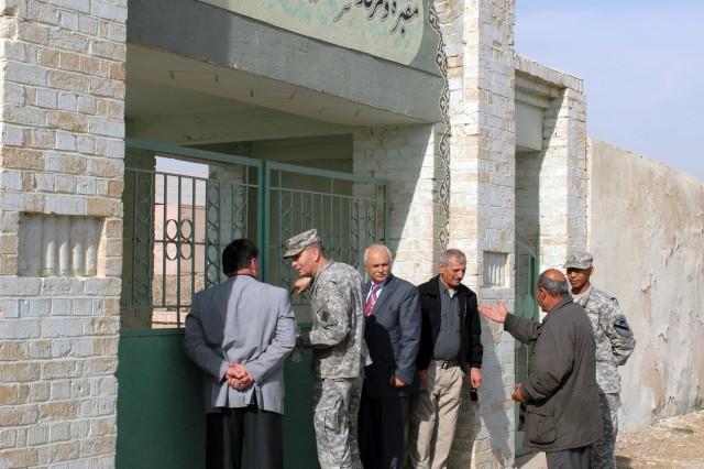 Officials from Bilawah and Tis'Ayn villages and officials from Forward Operating Base Warrior in Kirkuk, Iraq, stand outside the gate to Sultan Saqi Shrine also on FOB Warrior, Feb. 5. The leaders are discussing future plans for the shrine and how they can allow local citizens to pay respects to the holy site.