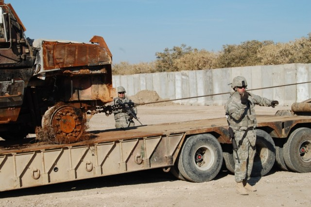 CAMP LIBERTY, Iraq - Combat mechanic, Spc. Scott Monroe of Gulfport, Miss., with the 890th Engineer Battalion, uses hand signals to back a wrecker up so that a battle-damaged vehicle can be repositioned onto a trailer during recovery training at the 890th Eng. Bn. motor pool Feb. 5.