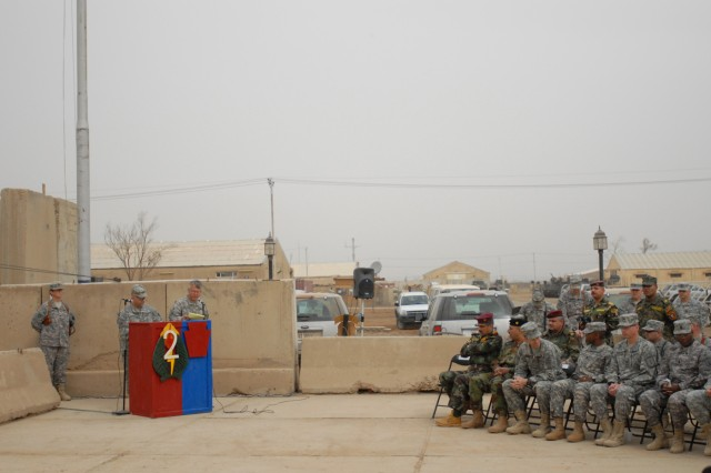 CAMP TAJI, Iraq - Col. Marc Ferraro (left, at podium), commander of  56th Stryker Brigade Combat Team, 28th Infantry Division, speaking through an interpreter, addresses visiting Iraqi military leaders during a Transfer of Authority ceremony Feb. 24. The event marked the Pennsylvania National Guard brigade's official start of its mission in Iraq. The brigade will be deployed in Iraq through late summer.