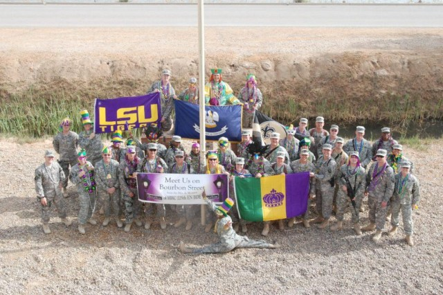"""CAMP LIBERTY, Iraq - Members of the Louisiana National Guard's 225th Engineer Brigade pose in front of their headquarters Feb. 24. The Soldiers won't let a deployment to Iraq stand in their way to celebrate Mardi Gras.  Donations from home and a """"joie-de-vive"""" keeps the good times rolling."""