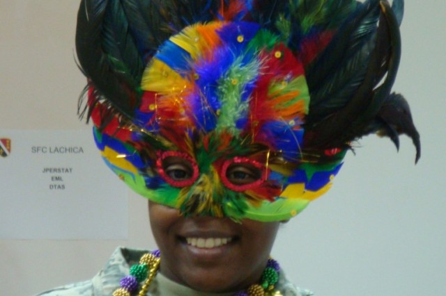 CAMP LIBERTY, Iraq - Sgt. RoKeisha Berymon of Alexandria, La., 225th Engineer Brigade, Louisiana National Guard, celebrates Mardi-Gras Feb. 24 in style by dressing up in the traditional holiday attire of colored beads and masks