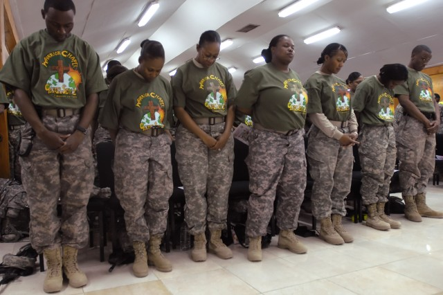 """BAGHDAD – Multi-National Division – Baghdad Soldiers in the Warrior Chapel Choir pray during the invocation of the """"African-American/Black History Month"""" Observance at Camp Liberty Feb. 22. The event highlighted the cultural advancements of all Americans since the founding of the United States in 1776."""