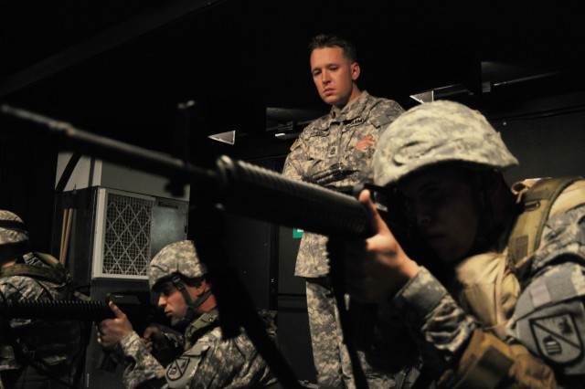 """Sgt. 1st Class Brent Church watches for proper marksmanship technique during virtual simulation training.  """"By watching Soldiers closely - their positioning, breathing, aiming, etc - we can tell how comfortable they are and encourage them to make adjustments until they feel completely relaxed with their weapon. Once that happens, they achieve the Army's goal,"""" said Church."""