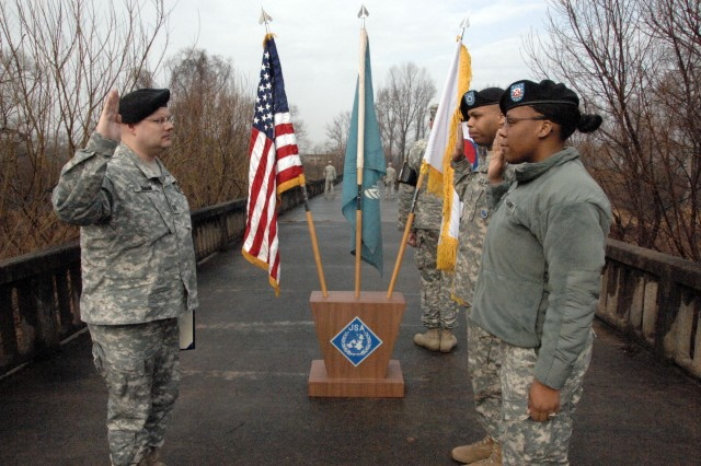 Capt. Tige Braun, 1-43 AMD administers the Army re-enlistment oath to Pvt. Keith Bell (right rear) and Pfc. Jasmine Bell (right front) on the Bridge of No Return, which crosses the DMZ at Camp Bonifas. They are the only Army couple to take the Army re-enlistment oath on the bridge. Additional photos from this event are available online at www.flickr.com/imcomkorea. - U.S. Army photo by Jim Cunningham