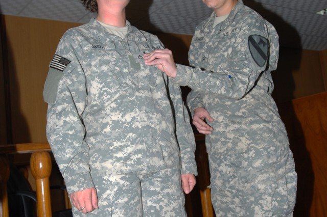 "CAMP LIBERTY, Iraq - During their joint promotion ceremony Feb. 21, Pfc. Roxanne Johnson (left), a military justice paralegal from Smithfield, N.C., receives her newest rank from fellow Soldier, roommate and best friend, Pfc. Tamara Smith, a paralegal assistant from East St. Louis, Ill.  Both took turns ""pinning"" rank on the other to honor their commitments to the Army and to friendship"