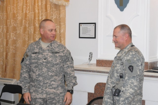 BAGHDAD - Col. Lee Henry (left), commander of the Texas Army National Guard's 56th Infantry Brigade Combat Team, 36th Infantry Division, Multi-National Division-Baghdad, talks to his Inspector General, Maj. Dean Dahle, of Wendell, Minn. prior to his promotion to Lieutenant Colonel during a promotion ceremony at Camp Victory on Feb 25. Dahle, a school teacher in El Paso, Texas, is serving his first tour to Iraq.