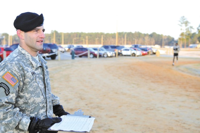 Staff Sgt. Keith Bach, HHC 1st BCT, grades runners at an Army Physical Fitness Test at Donavon Field, Feb. 24 at Fort Stewart, Ga.