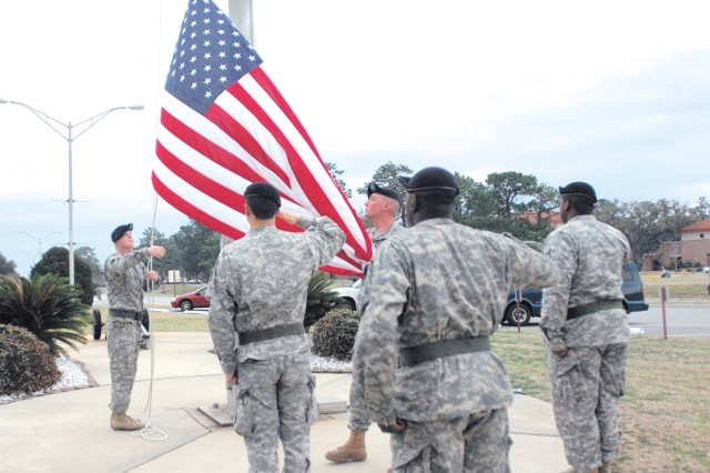 Members of 3/17 Cavalry salute the Flag as it is being lowered at the end of the duty day, Feb. 18, at Hunter Army Airfield. The Soldiers are a part of a month-long flag detail.