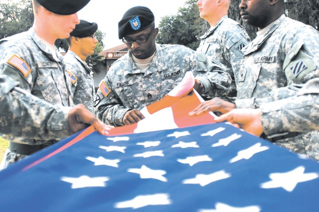 Staff Sergeant Kendricks Fields, HHT, 3/17 Cav. folds the American Flag at the end of the duty day, Feb. 18, at Hunter.