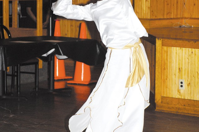 """Warrant Officer Lacey Washington, a supply systems technician with the 226th QM Co., performs a spiritual dance at Rocky's Feb. 19 in honor of Black History."""""""