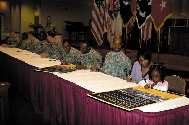 Third Infantry Division Command Sergeant Major Jesse Andrews signs the Army Warrior Healthcare Covenant Feb. 19 at the Main Post Chapel.  In addition, Johann Brown, A Co, WTU and his wife Monica watch as their 4-year old daughter, Anaia Brown signs the document too.