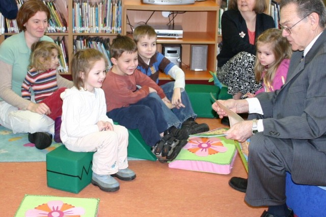 David Koralewski, right, reads to a group of children during the weekly reading the children's story hour at the Ledward Library.