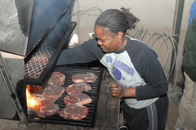 BAGHDAD-Garna Patrick, a East Life Support Area Morale Welfare and Recreation staff member, prepares steaks for Soldiers returning from missions at a barbecue cook-off Feb.22 at the East MayorAca,!a,,cs Cell on Camp Liberty.